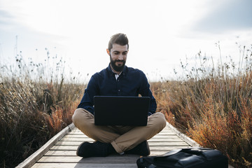 Freelancer working in nature looking contentCasual man browsing laptop while lounging in beautiful fresh nature sitting on walkway in fields.