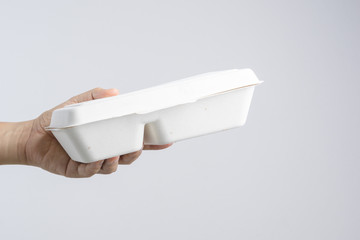 Hand holding Thai food in plant fiber paper food box