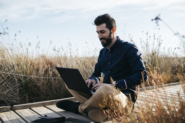 Content man enjoying working in natureBearded casual man relaxing on pathway in dry rural fields surfing laptop in sunlight looking happy.