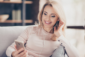 Close up portrait of attractive pretty woman  siting on couch in living room, having, using earphones, holding smart phone, listening music, looking at screen of telephone in hand
