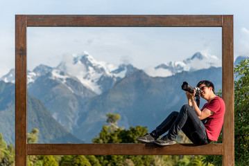Young Asian male photogrpher sitting on wooden frame of Mount Tasman and Mount Cook
