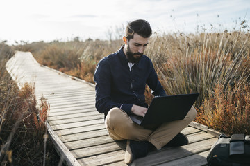 Man?working with laptop on?wooden?pier