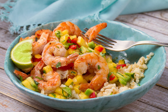 Shrimps with mango avocado and red pepper salsa on cauliflower rice
