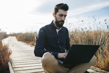 Casual man with laptop in natureConcentrated man relaxing on wooden pathway in field browsing laptop in sunlight.