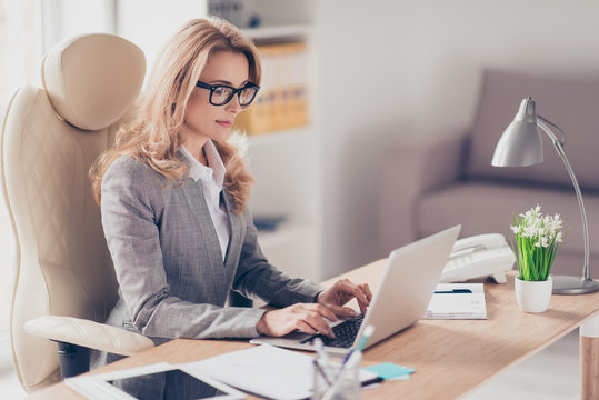Confident serious experienced qualified beautiful smart woman with blonde hair wearing grey suit and white shirt is typing letters to her clients and business partners, sitting at the table in office