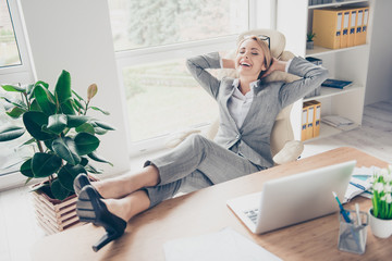 Cool, cheerful, smiling director hold legs in shoes on table, sitting on chair at desktop in workstation, having hands behind the head, remembering good memories, dreaming