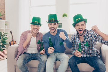 Happy Saint Patrick's day! Attractive, handsome joyful guys with bristle shouting screaming with open mouth and raised fists watching football game, sitting on couch, having beverage, lager