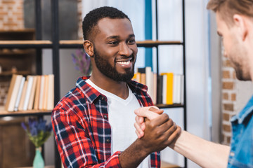 selective focus of young multiethnic men holding hands and smiling each other Wall mural