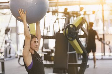 Asian female doing exercise with gymnastic ball in fitness center.