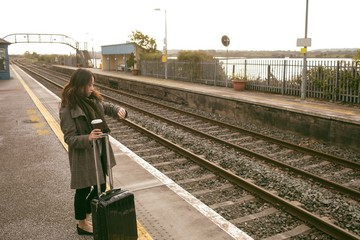 Female executive waiting for train with luggage