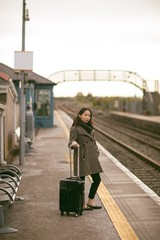 Woman waiting for the train with luggage