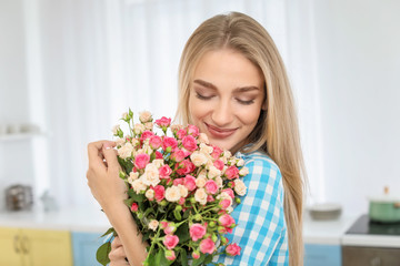 Beautiful young woman with bouquet of roses at home
