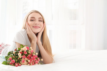 Beautiful young woman with bouquet of roses on bed at home