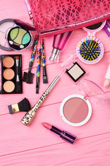 Flat lay cosmetics, tools and pouch. Decorative cosmetic set on colorful background, top view. Woman fashion makeup essentials.