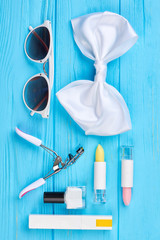 Sunglasses, bow-tie and cosmetics. Decorative cosmetics and stylish accessories, blue wooden background. Beauty and fashion concept.
