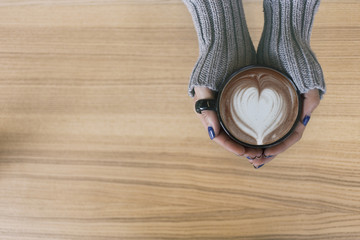 Top view female hands holding a cup of hot coffee with heart shape latte art. with copy space.
