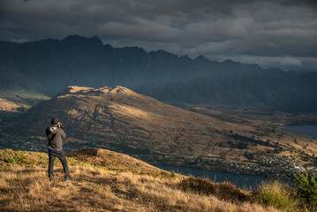 Young male photographer taking photo of scenery in Queenstown