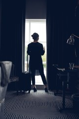 Woman using mobile phone in hotel room