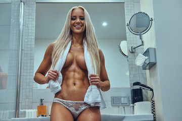 Young sexy naked blonde girl holding a towel on the shoulders.