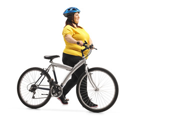 Overweight woman pushing a bicycle