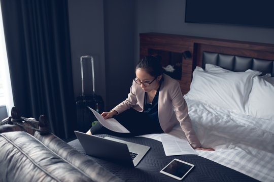 Woman reading document while working on laptop