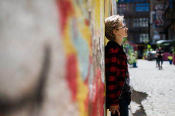 Young beautiful blonde sad woman in black glasses on the street with graffiti. Half-turned urban portrait