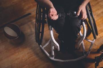 Disabled man adjusting belt of wheechair