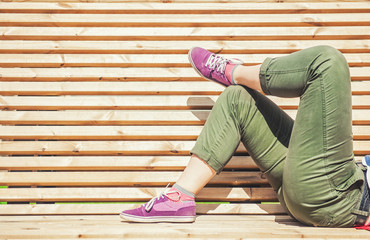 Legs of woman in green pants and purple sneaker lying on the bench
