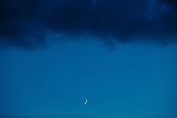 moon on background of blue sky and dark clouds. new phase.