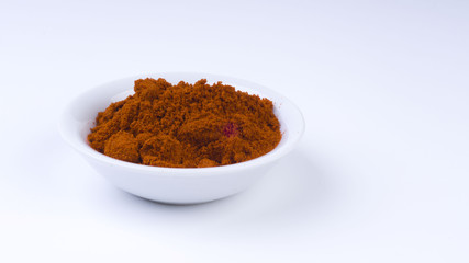 Red Chilly Powder in a bowl on white background.Selective focus and crop fragment.