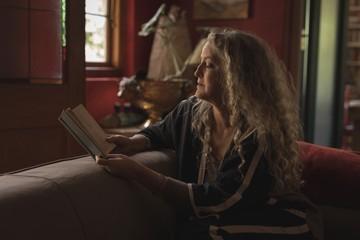 Mature woman reading book on sofa