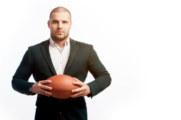 A young bald man in a white shirt, green suit holds a rugby ball poses on a white isolated background