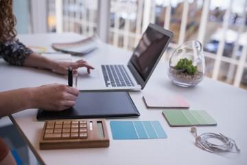 Female graphic designer using graphics tablet at desk