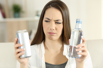 Confused girl deciding between soda refreshment and water