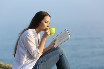 Woman drinking coffee and reading a book outdoors