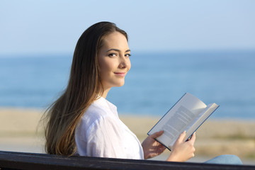 Woman reading a book and looking at camera