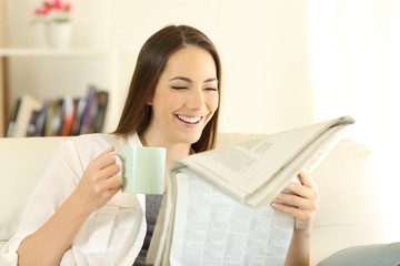 Woman reading a newspaper and holding a coffee cup