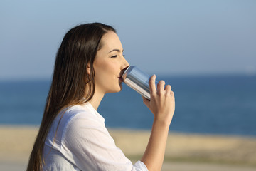 Woman drinking soda from a can outdoors on the beach