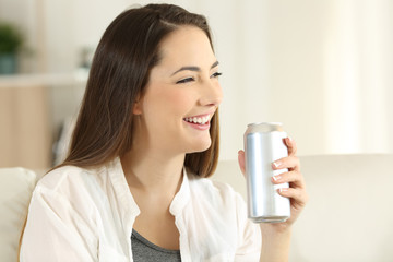 Female holding a soda can on a couch at home