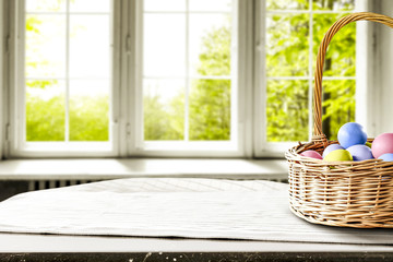 Easter eggs on wooden table in basket and background of window of spring.
