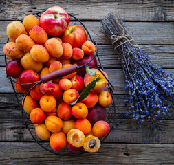 Apricots, Fruits in a metal basket on a vintage wooden background.Lavender, Flowers Bouquet.Food or Healthy diet concept.Super Food.Vegetarian.Copy space for Text.selective focus.