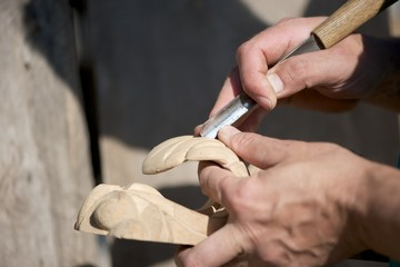 Closeup picture of woodcarving process. Male hands, tools and the wooden piece.
