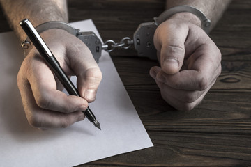Men's hands with handcuffs fill the police record, confession. on top see the police investigative detective. Arrest, bail, criminal, prison. Close-up