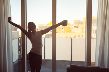 Sleepy woman stretching,drinking a coffee to wake up early in the monday morning sunrise.Starting your day.Wellbeing.Positive energy,productivity,happiness,enjoyment concept.Morning ritual