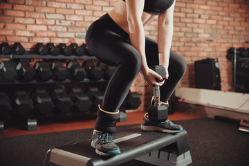 Young sportive woman exercising in gym using step platform with weighting. Concept of weight loss