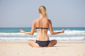 A blonde woman facing away from the camera doing yoga on a beach in a a bikini.  Beautiful sea in the background.