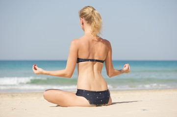 A young woman facing away from the camera doing yoga on a beach. Beautiful sea in the background.