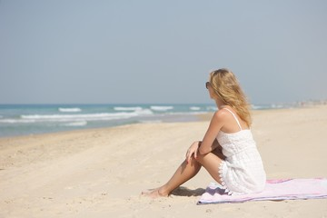 A young woman wearing white lacy dress and sunglasses sitting sideways on a pink blanket at a beach in Israel. Wavy sea in the background.