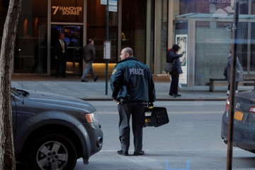 A New York Police Department officer carries a box into a building, containing IBT Media, parent company of Newsweek Media Group, in New York