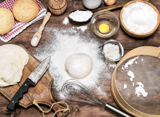 scattered wheat flour on the table, next to raw yeast dough